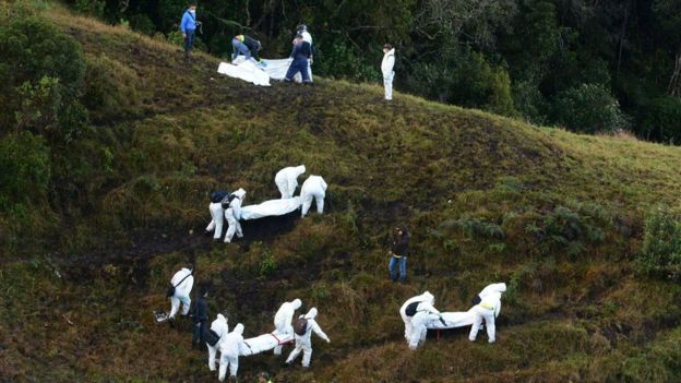Rescue workers carry the bodies of victims of an airplane that crashed in a mountainous area outside Medellin, Colombia, Tuesday, Nov. 29, 2016