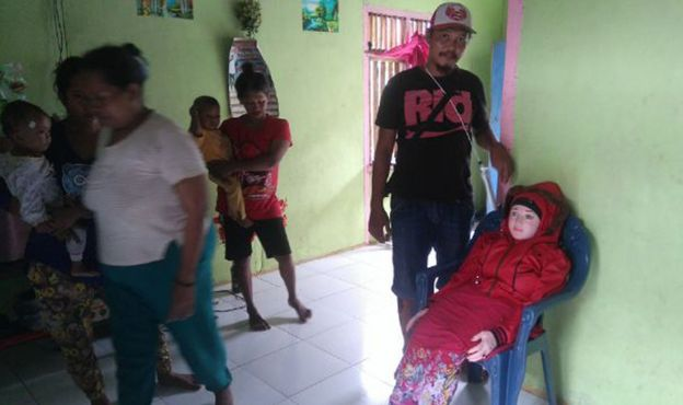 This recent undated handout picture released by Indonesian police and made available on 3 May 2016 shows an Indonesian man standing next to a sex doll (R-on chair) at a home in Banggai in Sulawesi.