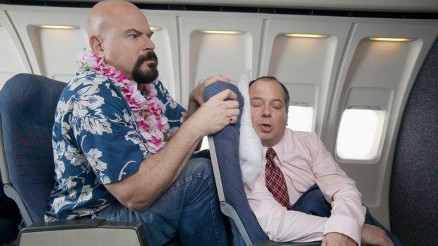 Un hombre muy incómodo en un asiento de avión