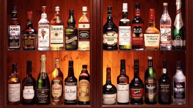 Uma prateleira cheia de garrafas de bebida alcóolica