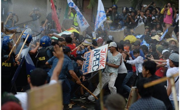 Philippine police fire water cannon as they clash with protesters parading down a street trying to voice their opposition to the Asia-Pacific Economic Cooperation (APEC) Summit currently taking place in Manila on 19 November 2015.