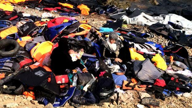 Migrantes rodeados de chalecos salvavidas