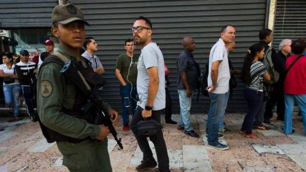 A Venezuelan soldier patrols as people queue outside a bank in Caracas in an attempt to deposit money, on 15 December 2016.
