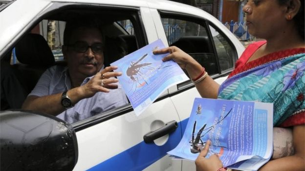 An Indian health worker distributes leaflets on a street in an awareness drive against the spread of dengue fever, a mosquito borne disease, in Kolkata, India,