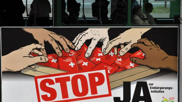 This file picture taken on 26 May 2008 in Basel shows commuters taking the tramway behind a poster of the hard right Swiss People's Party depicting multi-coloured hands grabbing Swiss passports