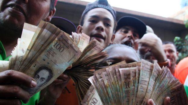 Personas con billetes de 100