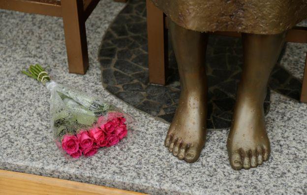 Flores deixadas aos pés de estátua colocada na Austrália