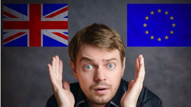 Человек с удивленным лицом и двумя флагами ЕС и Британии