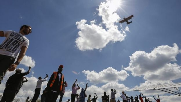 A vintage biplane flies over spectators during the Vintage Air Rally held at Nairobi National Park, in Nairobi (27 November 2016)