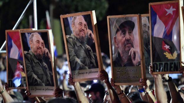 Personas sosteniendo cuadros con fotos de Fidel Castro.