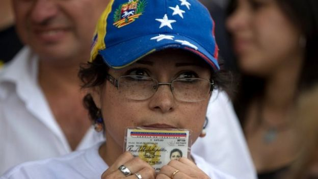 A woman holding her ID cards waits in line to sign a petition to initiate a recall referendum against Venezuela's President Nicolas Maduro in San Cristobal, Venezuela, Wednesday, April 27, 2016.