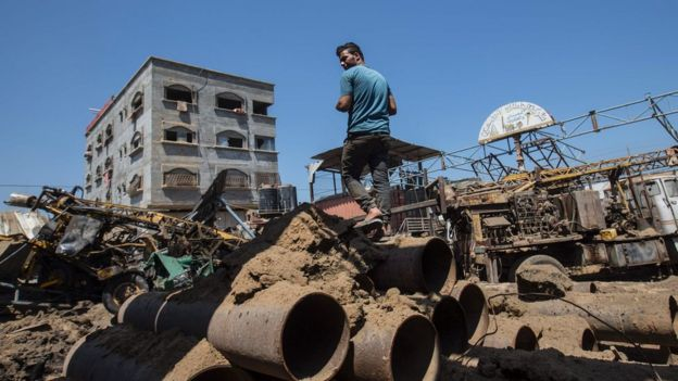 Palestinian man looks at damage following Israeli air strike on workshop in Gaza City on July 2, 2016