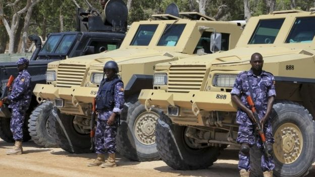 Amisom troops beside armoured vehicles