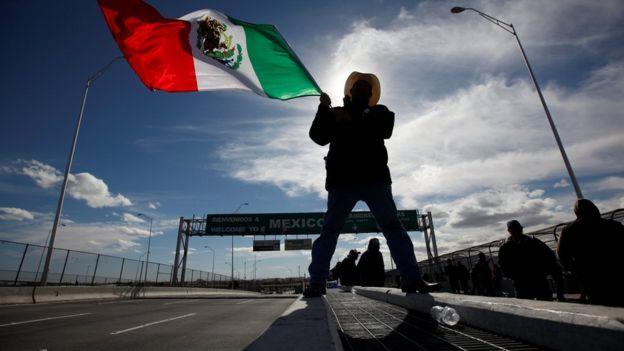 Un hombre ondea una bandera de México cerca del cruce fronterizo con EE.UU.