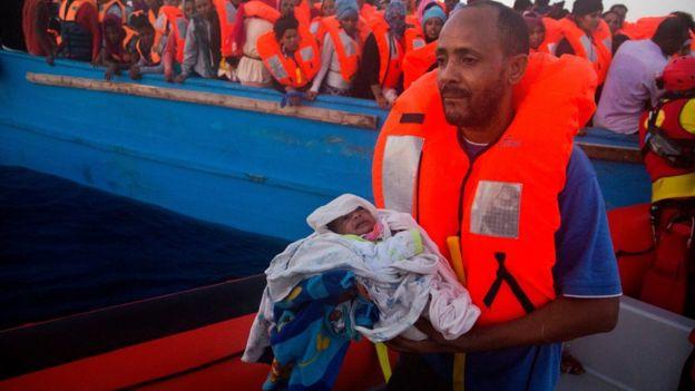 Un hombre carga un bebé