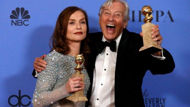 La actriz Isabelle Huppert y el director holandés Paul Verhoeven muestran dos premios globos de oro. El director sonríe y ella se muestra seria.