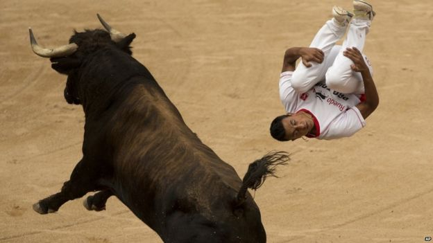 A man jumps over a bull during a competition at the San Fermin festival in Pamplona, Spain, 11 June