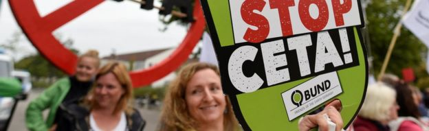 Consumer rights activists hold banners to protest against the Comprehensive Economic and Trade Agreement (CETA)