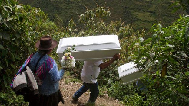 Familiares de víctimas de la guerra interna en Perú cargando féretros.