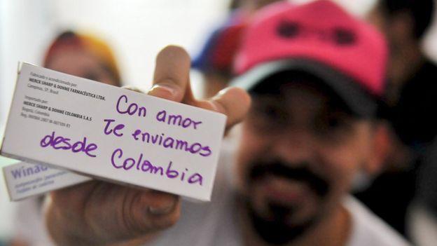 Un hombre con una caja de medicina enviada desde Colombia