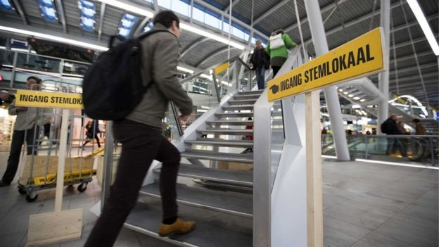 Dutch commuters line up at a polling station to vote in parliamentary elections at Utrecht Central Station, in Utrecht, the Netherlands, 15 March