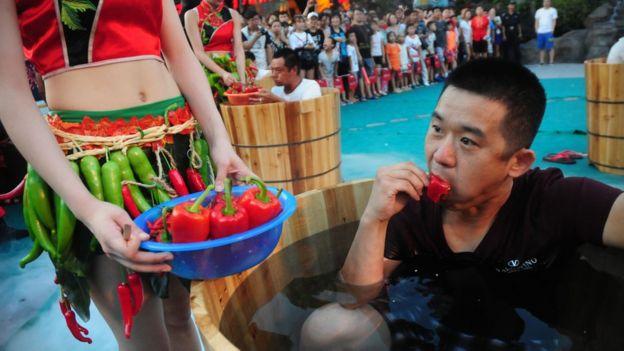 Hombre en un barril de agua mientras come chiles.