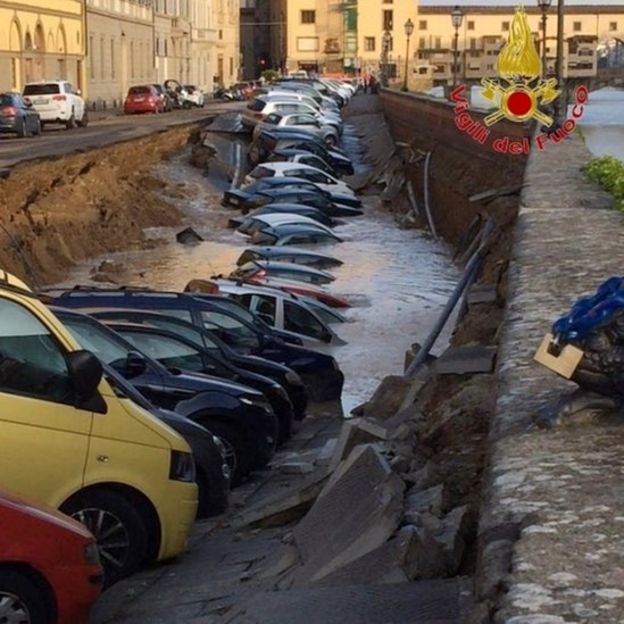Photo provided by Italian fire service shows cares in large ditch, some of them underwater, on embankment of River Arno in Florence (25 May 2016)