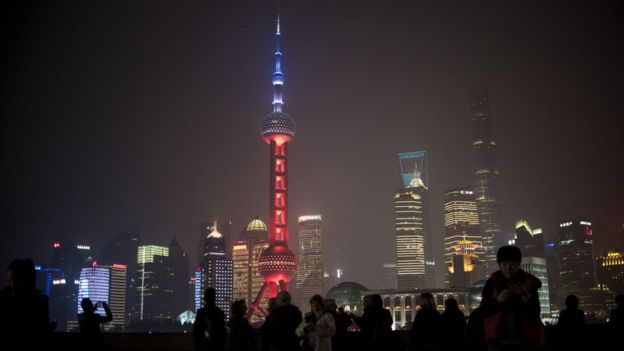 (C), in the Lujiazui Financial District in Pudong, is lit in red, white and blue, resembling the colours of the French flag, in Shanghai on November 14, 2015,