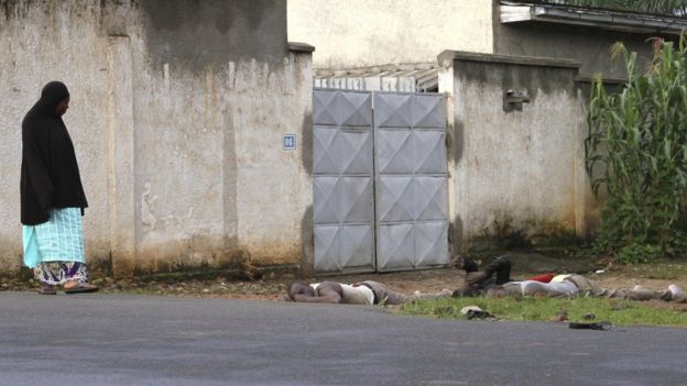 A resident looks at bodies of men killed during gunfire in the Nyakabiga neighbourhood of Burundi's capital Bujumbura