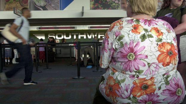 Pasajero con sobrepeso sentando frente a unos mostradores de aerolínea