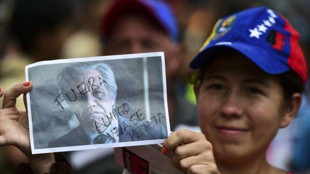 Una mujer con una foto de Luis Almagro