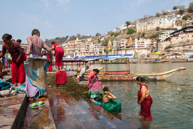 Pilgrims bathe in the Narmada River on the ghats at Omkareshwar