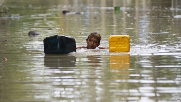 A flood-affected resident swims through floodwaters in Kalay, upper Myanmar's Sagaing region on 3 August 2015