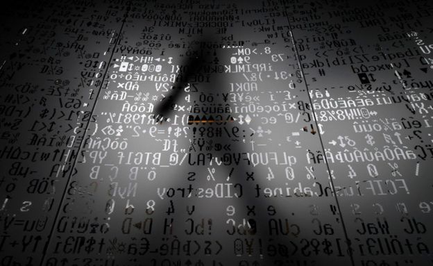 A silhouette of a man walking behind a glass wall with machine coding symbols at the headquarters of Internet security giant Kaspersky in Moscow