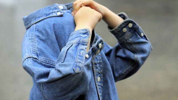 Niño se cubre rostro con chaqueta