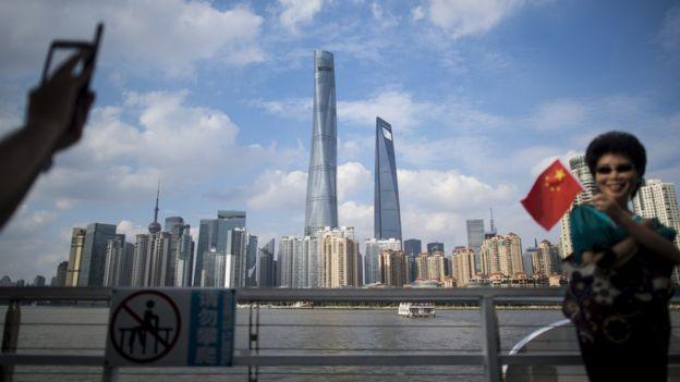 Mujer con bandera china frente a vista de Shangái