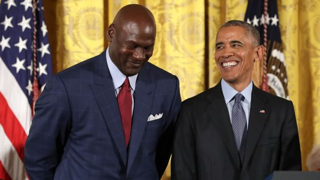 Barack Obama smiles up at National Basketball Association Hall of Fame member and legendary athlete Michael Jordan