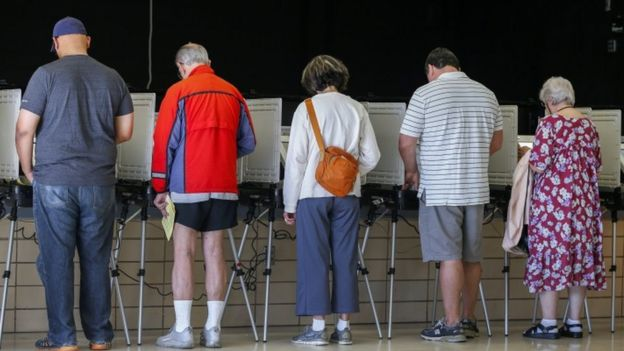 Votantes de espaldas emitiendo su voto.