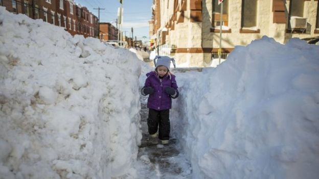A girl walks through a narrow shovelled path in Philadelphia, Pennsylvania (24 January 2016)