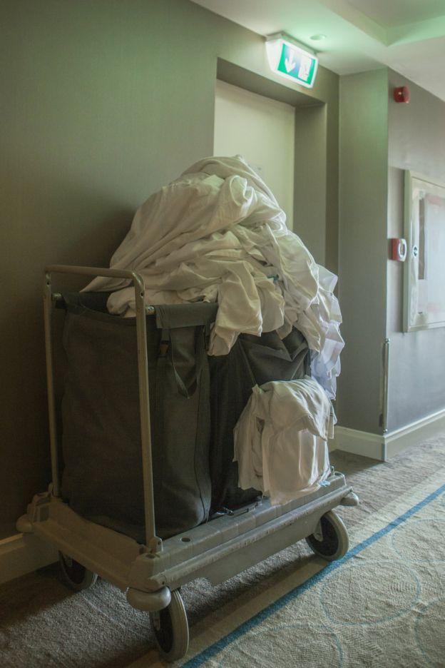 Carrito con toallas sucias apiladas en el corredor de un hotel