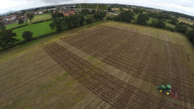 Aerial shot of field being ploughed by driverless tractor