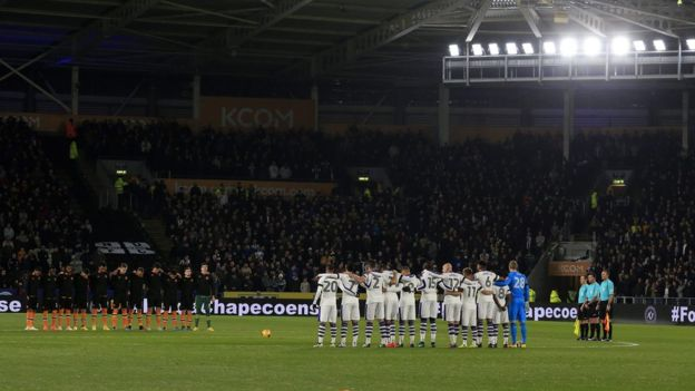 Hull and Newcastle players pause in tribute for the members of the Brazilian team Chapecoense