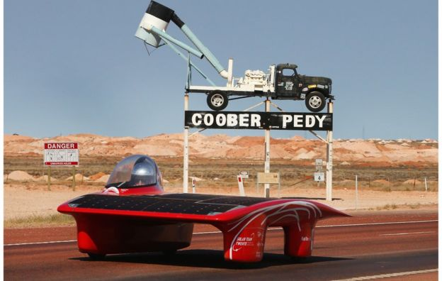 A handout photo taken and received on 21 October 2015, shows Red One of Solar Team Twente Netherlands leaving Coober Pedy as they race on day four in the Cruiser Class of the 2015 World Solar Challenge