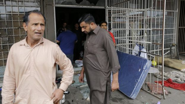 Man stands outside looted shop with broken glass on the floor