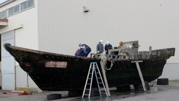 This picture taken on November 24, 2015 shows coast guard officials investigating a wooden boat at the Fukui port in Sakai city in Fukui prefecture, western Japan after the ship was found drifting off the coast of Fukui.