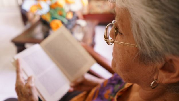 Una mujer mayor lee un libro.