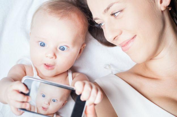 Bebé con cámara en teléfono y mamá