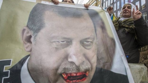 Kurdish people display a picture of Turkish President Tayyip Erdogan during a protest outside an EU-Turkey summit in Brussels