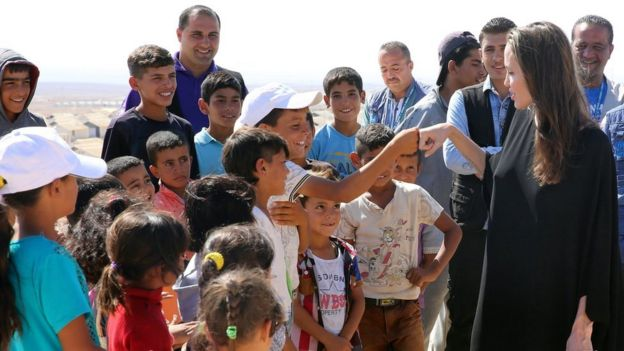 US actress and UN goodwill ambassador Angelina Jolie bump fists with a Syrian boy during her visit to Azraq Syrian refugee camp, 90 Km east of Amman, Jordan