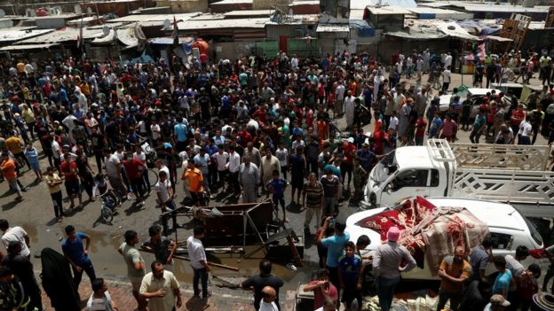 People gather at the scene of a car bomb attack in Baghdad's mainly Shia district of Sadr City